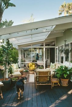 patio with white beams, strung lights, California feel. Love the plants and dark wood floor in contrast to the white house/beams.