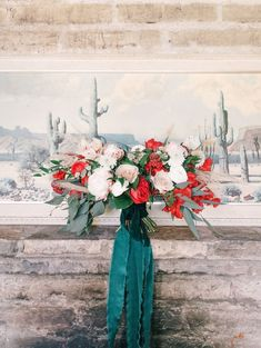 Red and beige bridal bouquet with green ribbon | Green wedding color inspiration | Bohemian Art Deco Desert Wedding featured by Martha Stewart Weddings