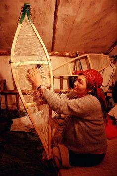 Cree woman, Elizabeth Brien, threads caribou hide lacing onto a pair of snowshoes. Quebec, Canada.