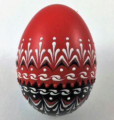 This is a chicken egg pysanka painted in red and black decorated with white, black and red wax. To create this egg, I use the pinhead method also known as the drop-and-pull pinhead method. In this method, mostly used in Poland, the Czech Republic, Slovenia, and Lithuania, a pin stylus is