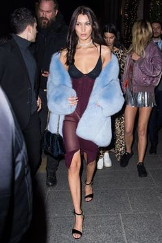 Bella Hadid's best street style looks. Black and maroon figure-hugging dress+black ankle strap sandals+blue oversized fur coat+black velvet chain shoulder bag+diamond jewellery. Fall Party Outfit 2016