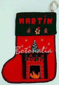 Calcetín de fieltro decorado con botones con formas navideñas: un osito con sombrero de papá noel, dos galletitas de gengibre, varias botas colgadas de la chimenea, un abeto (adorno) decorado y varias estrellitas diminutas.