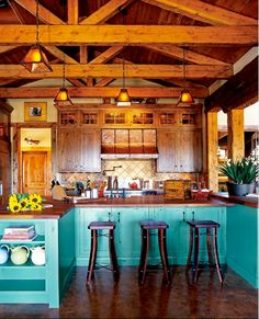 Stunning rustic kitchen - Warm wood stains against teal painted cabinets with amber lighting fixtures. CabinetsAndDesigns.net