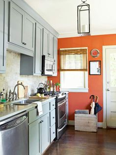 This small kitchen features soft grey cabinets paired with a spicy orange accent wall.