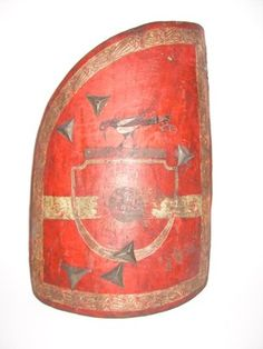 Hussar shield, rectangular with a rounded-off upper right corner and of rounded horizontal section. It is made of wood, the exterior covered with gesso and painted vermillion with a white border decorated with a geometrical vegetal scroll, across the centre is a white band. It is painted with an inescutcheon of vermillion with a black sun with gold rays, a continuation of the white band and crest in the form of a crow in black with white flashes standing on a black scroll. The inside is…