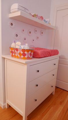 I love this changing table idea. Even though we're having a boy! This layout with the basket and the shelf is very handy.