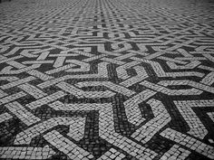 Pedra portuguesa sidewalk in Lisbon. The pattern is regular, but the individual components (stones) that make it up aren't.