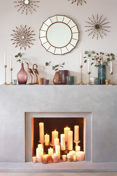 Create a modern look by layering different sized candles within your fireplace.