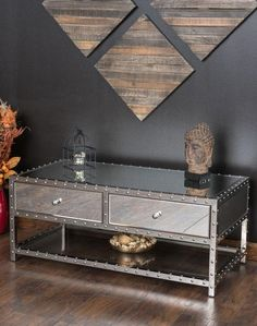 Every inch of the Brielle Mirrored Coffee Table will keep you in awe. Its nail head trim and mirror panels coupled with its silver finish brings an industrial yet luxurious design to your home. Two drawers with mirrored knobs provide the perfect blend of practicality and style.