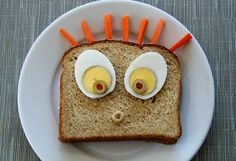 Surprised sandwich! hard boiled egg slices, green olives with pimento, sliced; Cheerio, carrot sticks