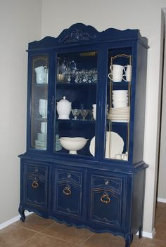 Navy china cabinet with white dishes. LOVE!