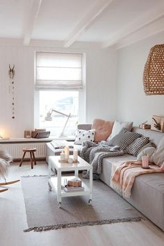 Cozy living room design idea. White blinds, grey sofa and small white coffee table on wheels.
