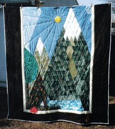 "This is number one of five   ""coming of age quilts"" that I will make for my niece and nephews.   They decide the important things in their lives at 19,   and I will make quilts reflecting these touchstones.   For Andrew, who is deeply involved in eco-tourism,   he wanted mountains with snow (he's a snowboarder),   sun, whitewater, his friend Joe's red car, and his two cats."