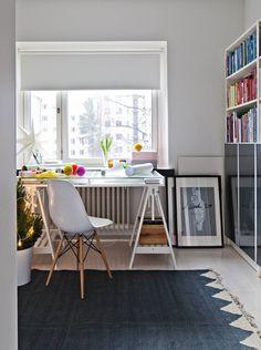 Työhuoneen ikkunan edessä on mainio paikka askarrella. Työtuolina on Charles & Ray Eamesin DSW-tuoli. Pöytä ja kirjahylly Ikeasta. Matto Perobasta.