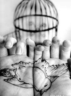 Holding a flying bird tattoo
