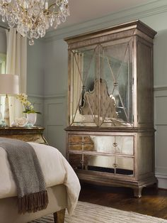 A mirrored armoire is the focal point of an elegant master bedroom.