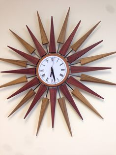 "Midcentury Modern sunburst wall clock. 30"" diameter. Bubinga and Teak with carbon fiber rods. By: Brownell Furniture."