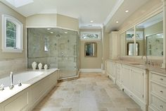 Traditional Master Bathroom with Limestone counters, Crown molding, Arched window, Handheld showerhead, Flat panel cabinets