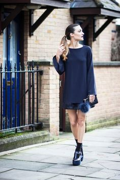 Anisa Sojka wearing navy Gioia Milano dress with fur appliqué and long sleeves, black Louis Vuitton clutch with navy See Me fur pom pom, and Filipe Souse blue suede wedge pumps with black high socks. Fashion blogger street style shot in London by Cristiana Malcica.