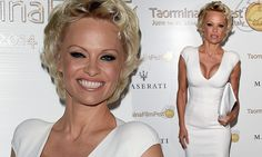 Pamela Anderson shows off famed cleavage in plunging white dress