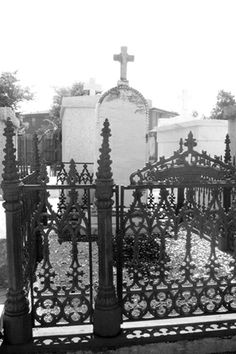 Fenced in grave - a typical sight in a New Orleans cemetery. Resembles the iron work on most French Quarter building. Some tombs or grave markers are circled in a wrought iron fence with a gate. Most are black, some are silver and some are red with rust, but they all have beautiful and intricate designs. http://www.thefuneralsource.org/cemla.html