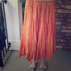 Vintage flowy skirt Burnt orange flowy long skirt with elastic waist. Has small metal stars woven throughout the skirt. Fully lined. Some stars are loose or have fallen off but that doesn't affect the overall look of the skirt. Size small but could fit S, M, L. Purchased in a consignment shop in Charleston, SC about 15 years ago. Thanks for looking. Gingerblu Skirts