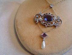 An amethyst, diamond, platinum, gold, and pearl necklace.