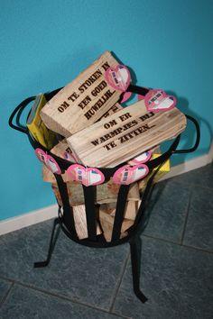 Vuurkorf gevuld met haardblokken. Op de haardblokken teksten gebrand. Geld erop bevestigd en cadeau gedaan ter ere van een huwelijksjubileum.