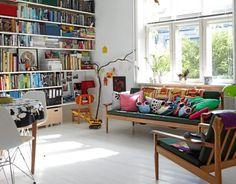 En liten stue virker luftig med hvite flater og mye lys. Sofa og lenestol er bruktfunn, i kroken er det gjort plass til leker for minsten. Lekekasser på hjul under bokhyllen. Ugleputene i sofaen er designet av Karen Bagge for det danske fairtradefirmaet Musahar.