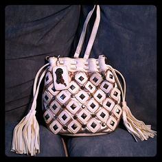 """Carlos Santana Cross-body purse This Carlos Santana purse is predominantly white with metallic studs on it and gold lame. I'd say the front looks like a pineapple, but that's not pretty enough. The picture shows it fairly well. The outside has tassels on both sides, a guitar with the word """"Carlos"""" on it, a draw string top and an extremely long strap.This barely used purse is beautifully presented. No marks or scuffs. No dirt left behind. If you're a fan of Carlos Santana, or you just can't…"""