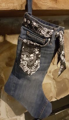 "This Christmas stocking is made with recycled blue jeans and has a tie belt and pocket flag made of black material with skulls on it. Stocking measures 18"" L x 7"" W and is big enough for all those Chr"