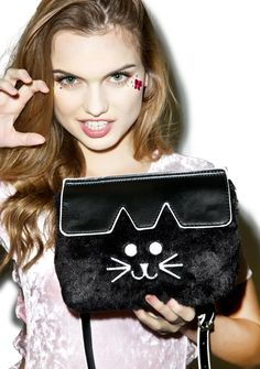 Nila Anthony So Catty Bag cuz yer a frisky little feline fiend. Yer gonna wanna pet this bag with its plush faux fur covered exterior and adorbz embroidered kitten face. Featuring an adjustable vegan leather shoulder strap and front flap, this cat bag will purrfectly hold all yer kitty essentials.