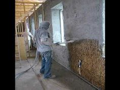 Spraying lime base cement on Straw bale house.