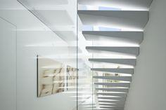 escalier suspendu à marches blanches et garde-corps en verre