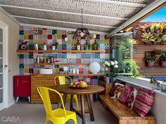 Na parede da bancada e do armário de teca no terraço, que já existiam, Renata instalou azulejos da Pavão Revestimentos. Mesa do Empório dos Móveis e cadeiras amarelas da Velha Bahia. Projetodo do terraço: Renata Fragelli