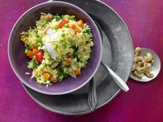 Indische Reis-Gemüse-Pfanne -     1 Zwiebel      3 Möhren (à 100 g)     1 Döschen Safranfäden (0,1 g)     2 EL Öl      50 g Cashewkerne      1 Zimtstange      6 Kardamomkapseln      4 Gewürznelken      2 Lorbeerblätter      250 g Basmatireis      ½ TL gemahlener Kreuzkümmel      Salz      600 ml mediterrane Gemüsebrühe      150 g Baby-Spinat      4 Kirschtomaten      300 g Erbsen (tiefgekühlt)     ½ Limetten      Pfeffer      1 Stück frische Kokosnuss (ca. 40 g)