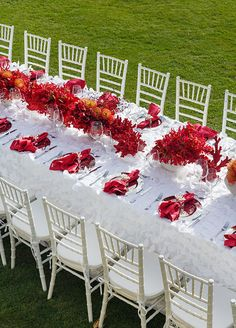 Textured white tablecloths were lined with vases overflowing with deep coral and red colored flowers. #weddingcenterpiece