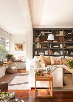 Salón bañado por el sol con sofá blanco en L, alfombra clara, librería negra y galería cerrada con banco y puf 00417767