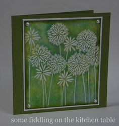 "By Anneke.  Uses Hero Arts negative stamp ""Flower Medley."" Press green and blue Distress Ink onto a craft sheet. Press the stamp into the ink. Spritz several times. Stamp onto watercolor paper. Sponge edges of panel. Attach to white mat, then green card. Add pearls."