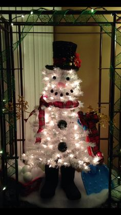 Snowman tree. Bought the hat at Michael's and spruced it up with holly and poinsettia.  Made the eyes and mouth with black cotton balls. Spray painted black the bigger size foam balls. used ribbon for scarf. Used my old boots for his feet