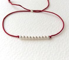 He encontrado este interesante anuncio de Etsy en https://www.etsy.com/es/listing/152965421/red-silk-thread-bracelet-with-10