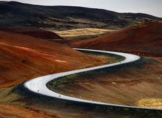 Iceland's Route 1, commonly referred to as the Ring Road, traverses over 800 miles of scenic countryside as it encapsulates the rugged interior highlands and connects remote regions of the country to the capital, Reykjavík. This photo of the S-curve on Route 1 was captured on an overcast, damp day. The result was a wet road reflecting a bright white sky amidst a myriad of color.