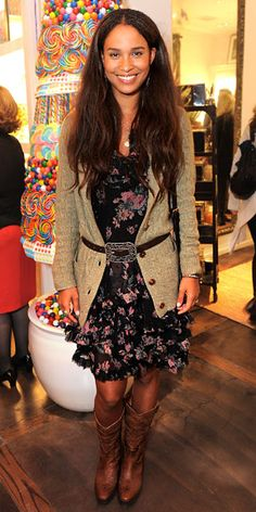 Joy Bryant in a floral frilly dress with a belted cable knit cardigan over it & cowboy boots.