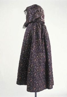 Hooded cloak, France, 1790-1810. Printed cotton with brances of lilies and small rosebuds on black ground.