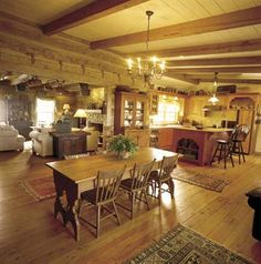 Big Sky Country This country dining area is warm and rustic. It features baskets hanging from the beamed ceiling, heart-pine flooring, views of the living room's massive stone fireplace, and the kitchen's recycled-church-pew...