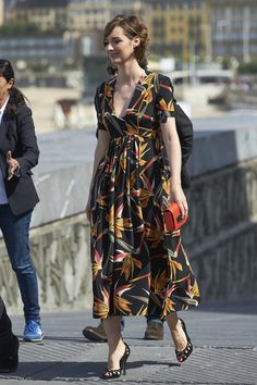 Louise Bourgoin in a printed dress with black heels and a red clutch