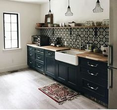 Lovely feature wall for an eclectic kitchen. The dark cabinets and bold patterned tiles are a great focal point