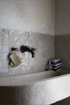 tiles and the limewash walls the stone sink. The wall mounted taps