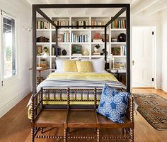 Architect Mark Reilly designed this bedroom around the minimalist canopy bed, aligning one shelf with the top of the mattress, continuing with equal-size book bays in the remaining space.