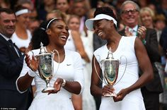 Serena (left) and Venus Williams hold their trophies after securing their sixth doubles championship at Wimbledon this evening